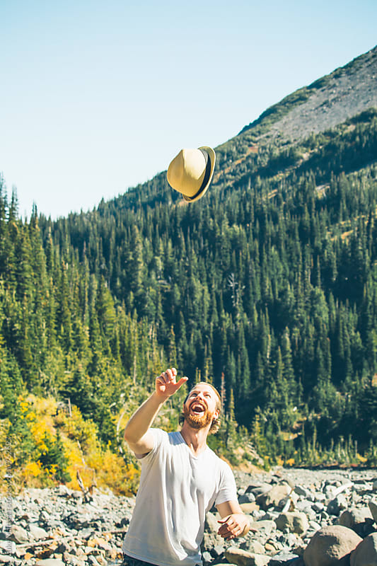 Blond Man With Red Beard Throwing Fedora Up In Celebration On Forest Hike by Luke Mattson for Stocksy United