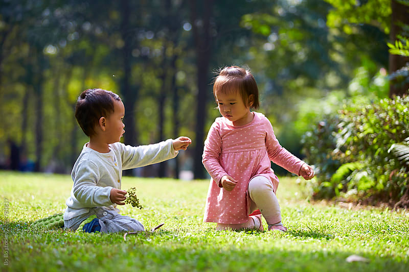 two lovely asian toddler playing together outdoor in the sunny park by cuiyan Liu for Stocksy United