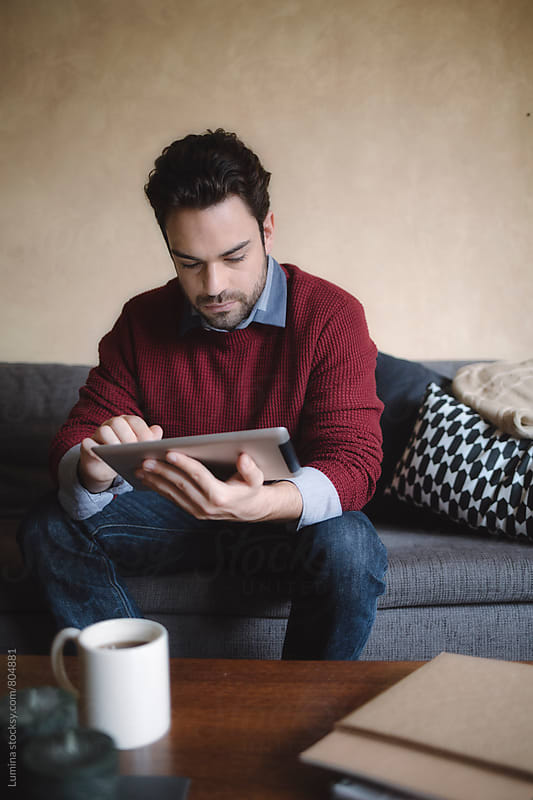 Caucasian Man Using a Tablet at Home by Lumina for Stocksy United