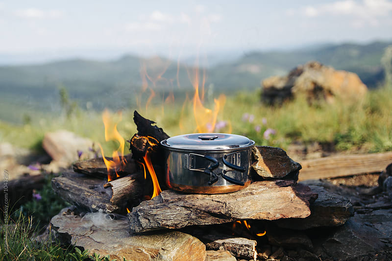 Cooking food on top of a mountain. by Justin Mullet for Stocksy United