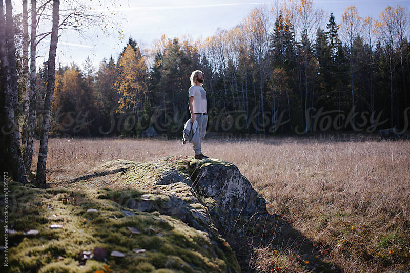 Man with standing on a rock in the nature of Sweden. by Koen Meershoek for Stocksy United