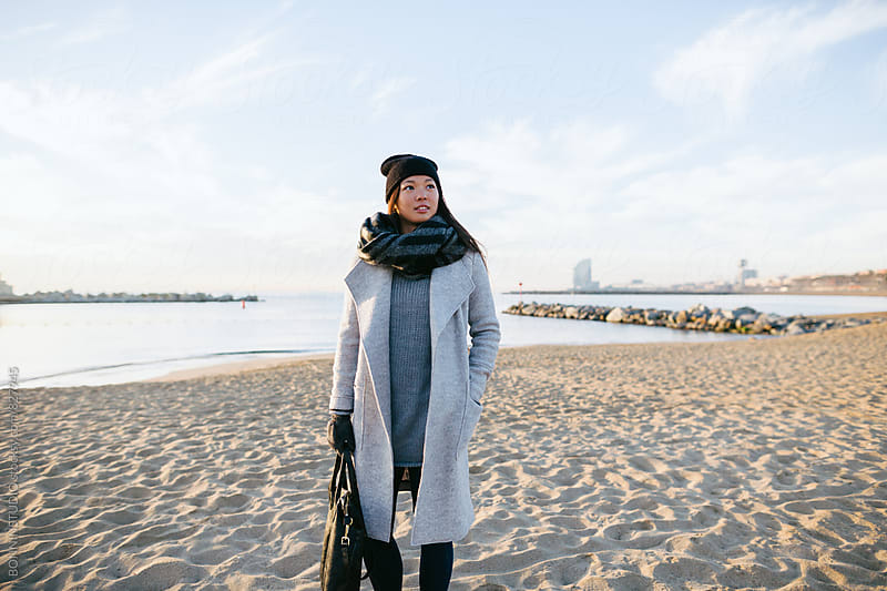 Asian woman walking on the beach on winter.  by BONNINSTUDIO for Stocksy United