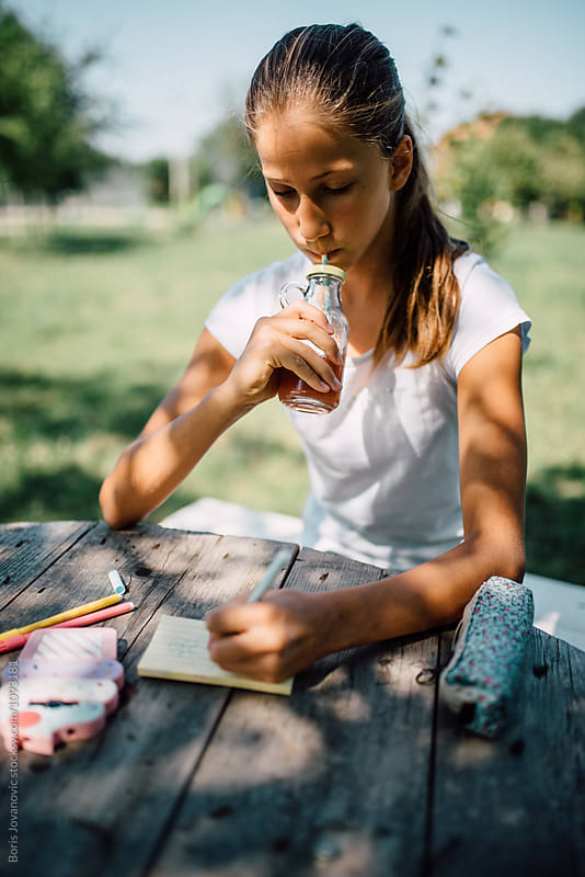 Young girl drinking juice and writing outdoor by Boris Jovanovic for Stocksy United