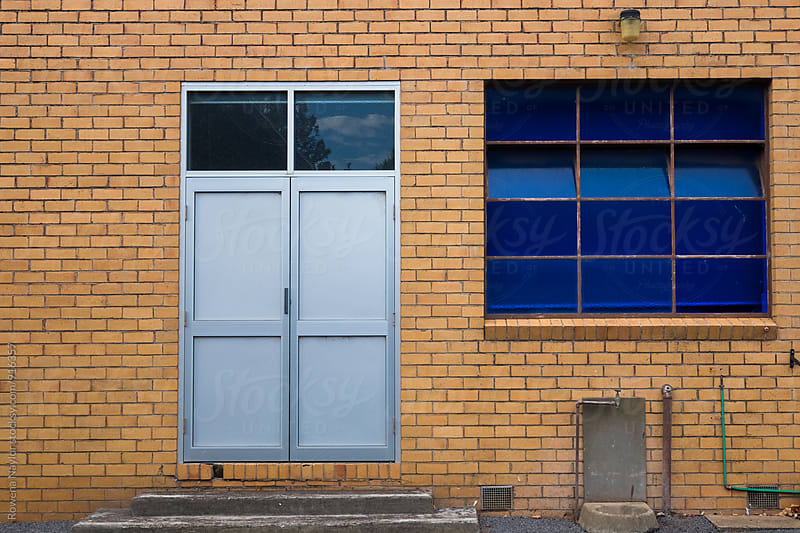 Industrial warehouse with blue glass windows by Rowena Naylor for Stocksy United