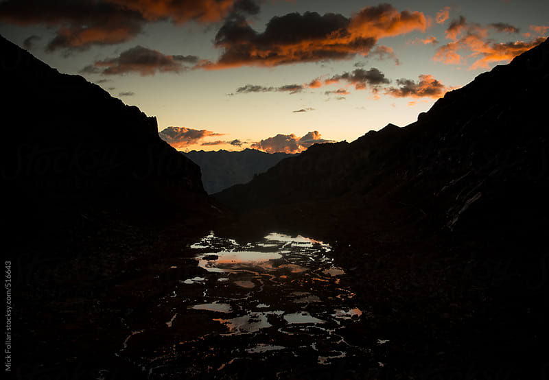 Mountain ponds and streams in dramatic sunset light with orange clouds by Mick Follari for Stocksy United
