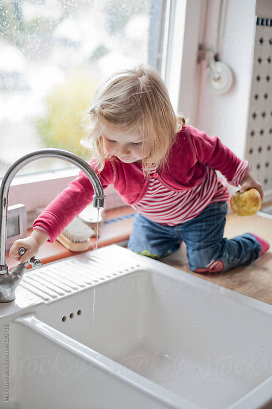 Toddler washing an apple in the kitchen sink by Ina Peters for Stocksy United
