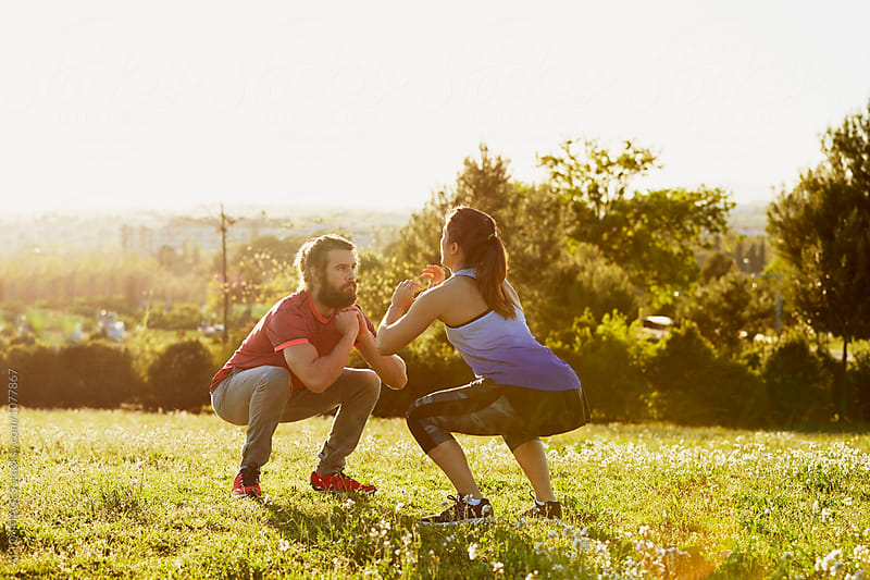 Determined Friends Doing Squats In Park by ALTO IMAGES for Stocksy United