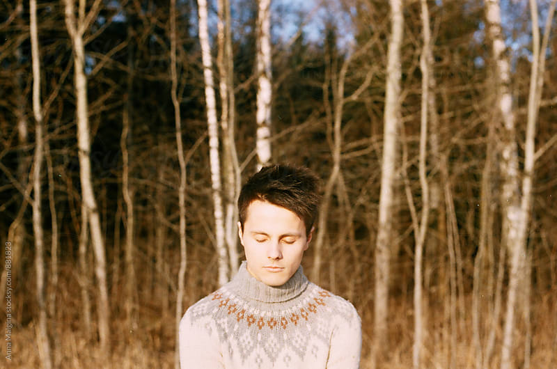 A film portrait of a young beautiful man in winter forest with closed eyes by Anna Malgina for Stocksy United