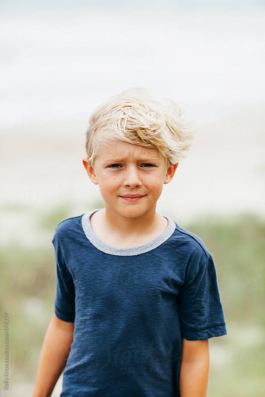 portrait of a handsome boy on a windy beach by Kelly Knox for Stocksy United