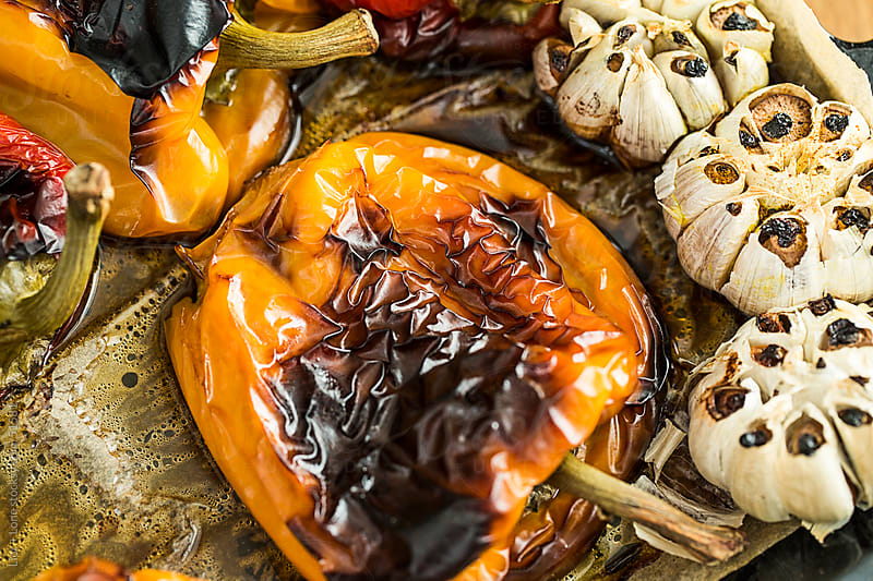 Colorful closeup of yellow roasted bell peppers and garlic by Lior + Lone for Stocksy United