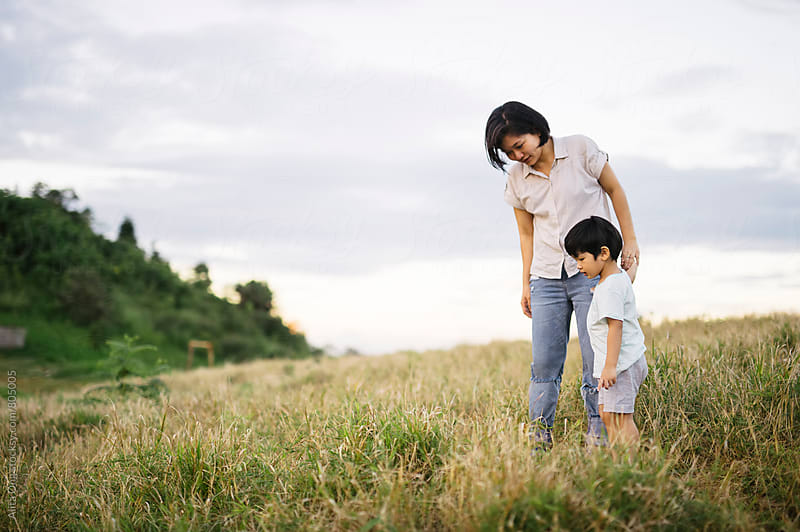 Mother and son exploring the grass field by Alita Ong for Stocksy United