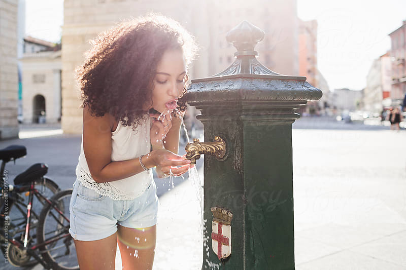 Beautiful girl drinking from a public fountain by michela ravasio for Stocksy United