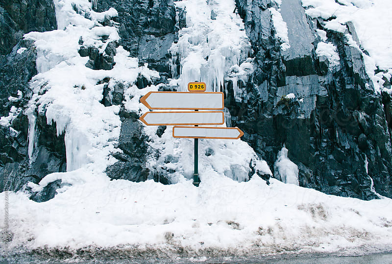 Road signs pointing all directions on a snowy crossing  by Denni Van Huis for Stocksy United