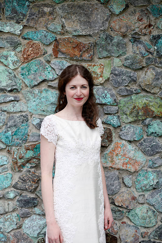 Beautiful bride in front of stone wall by Jennifer Brister for Stocksy United