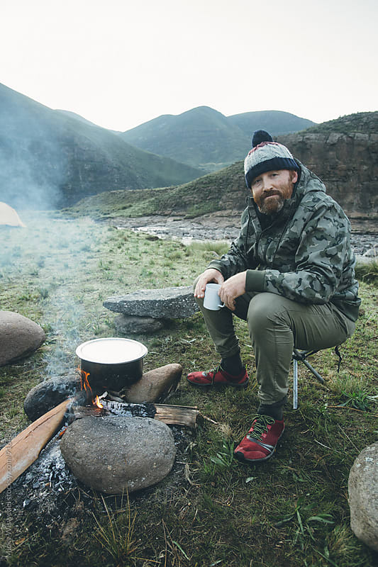 Outdoorsman cooking by a camp fire in the mountains by Micky Wiswedel for Stocksy United