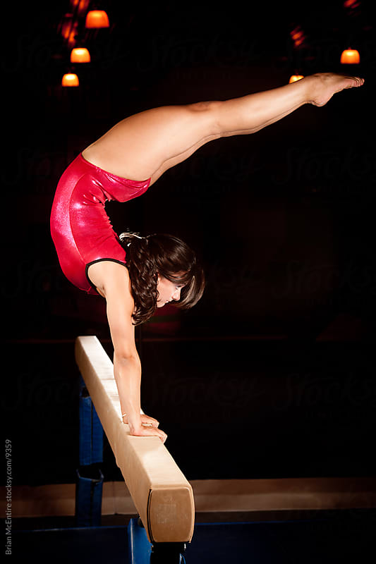 Amazing gymnast balances on beam with legs extended by Brian McEntire for Stocksy United