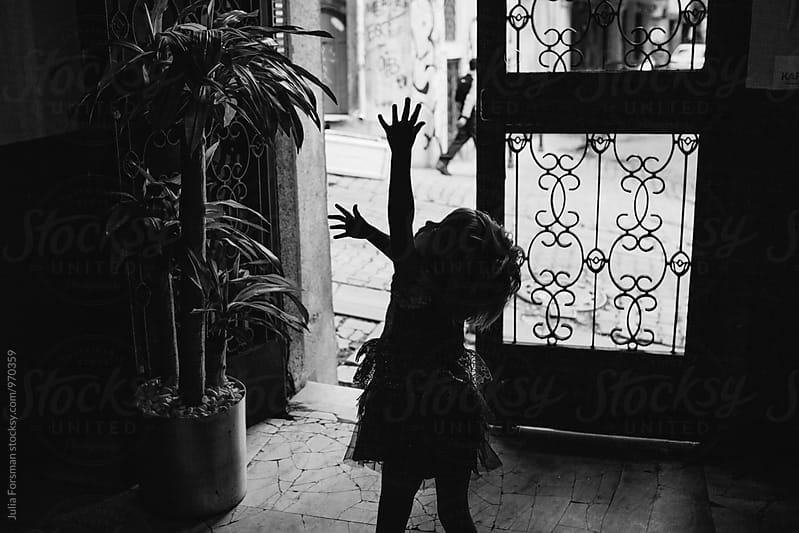 Silhouette of little girl waving her arms in the air on her way outside. by Julia Forsman for Stocksy United