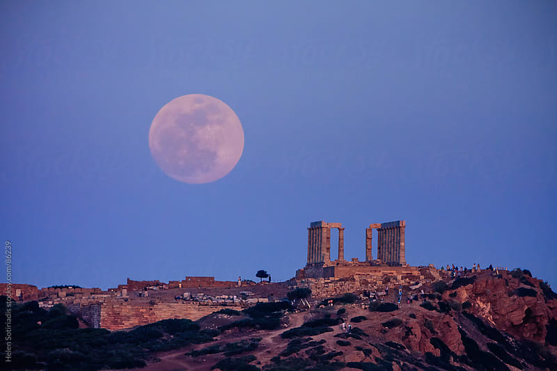 The moon rises beyond a Greek temple. by Helen Sotiriadis for Stocksy United