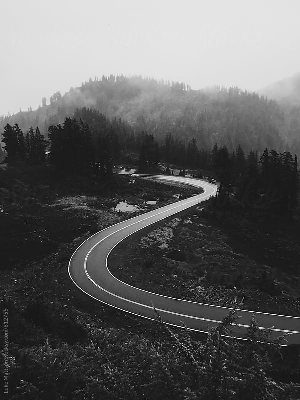 Curved Two Lane Road Winding Through Foggy Pine Forest In Mountains by Luke Mattson for Stocksy United