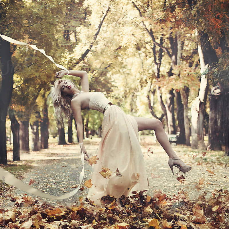 A beautiful young woman surrounded by leaves with silk tapes on her hands by Jovana Rikalo for Stocksy United