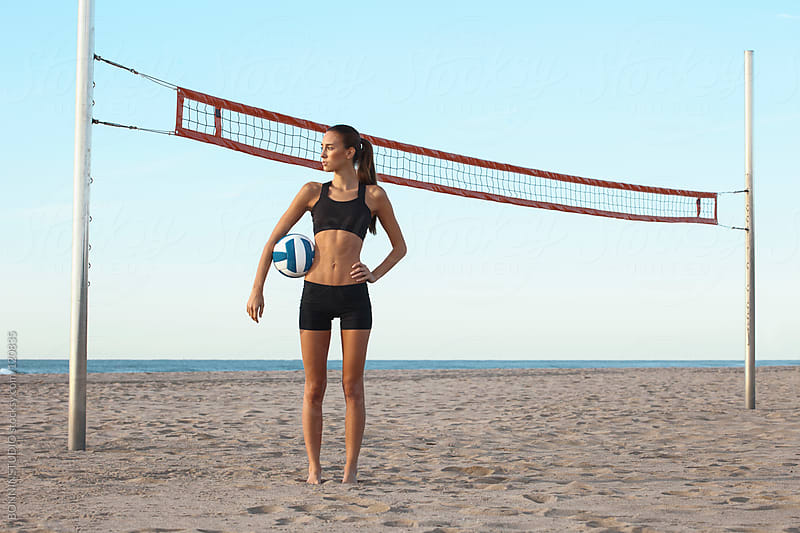 Beach volleyball. Sporty woman standing with ball. by BONNINSTUDIO for Stocksy United