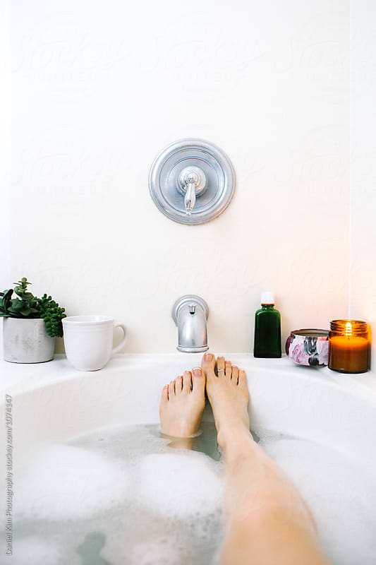 Feet up in bathtub by Daniel Kim Photography for Stocksy United