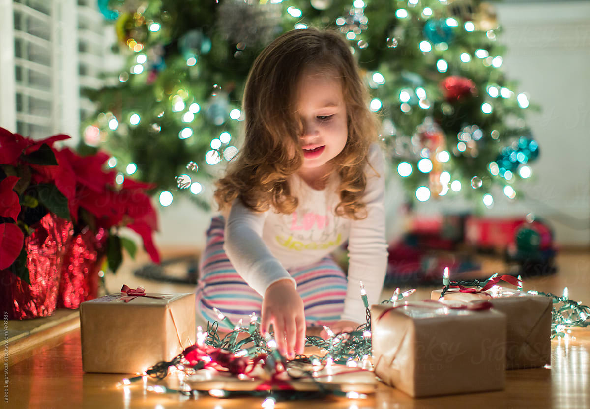Toddler Playing With Christmas Gifts And Holiday Lights | Stocksy United
