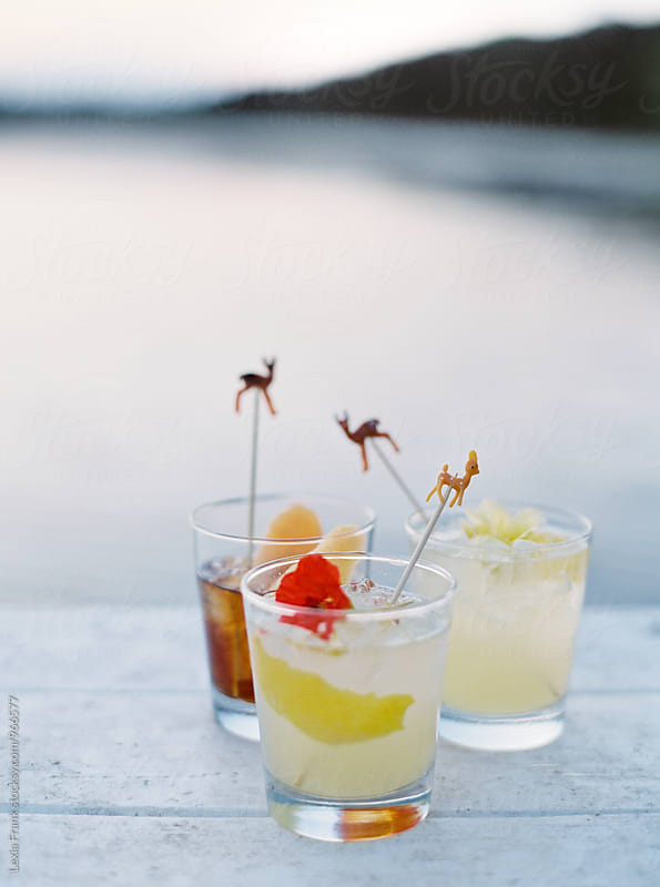3 cocktails on the dock of a lake with deer cocktail stir sticks by Lexia Frank for Stocksy United