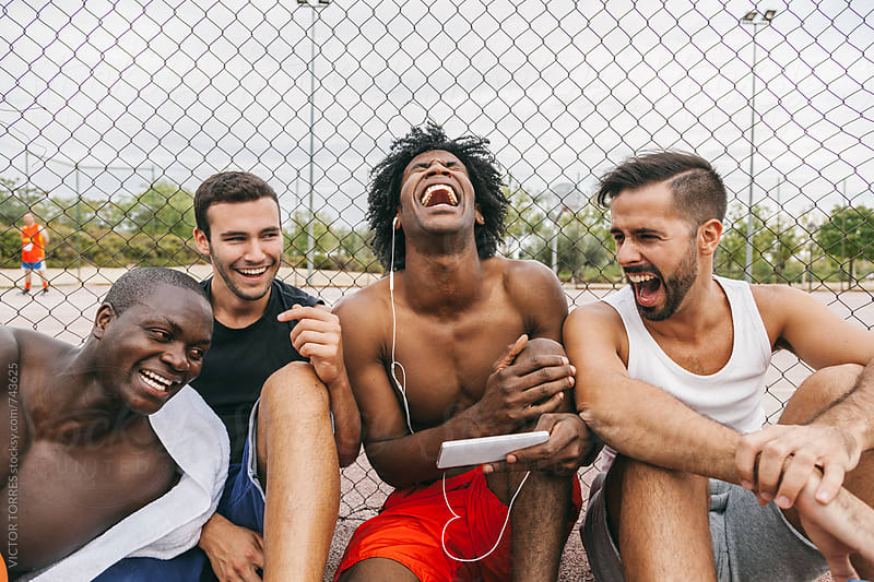 Friends Having Fun During a Rest After a Street Basketball Game by Victor Torres for Stocksy United
