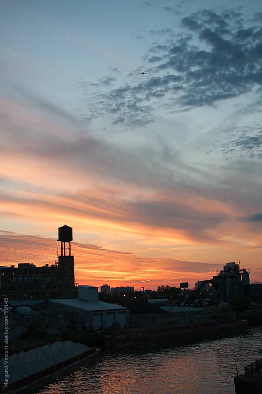 sunset over an industrial landscape by Margaret Vincent for Stocksy United