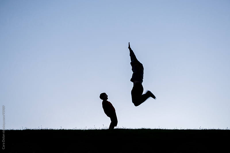 Silhouette of a boy laughing as his father leaps in the air in a field at sunset by Cara Dolan for Stocksy United