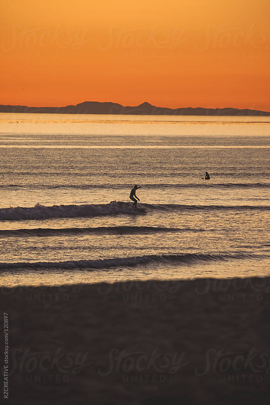 Surfer silohuetted against a warm orange sunset in California. by RZ CREATIVE for Stocksy United