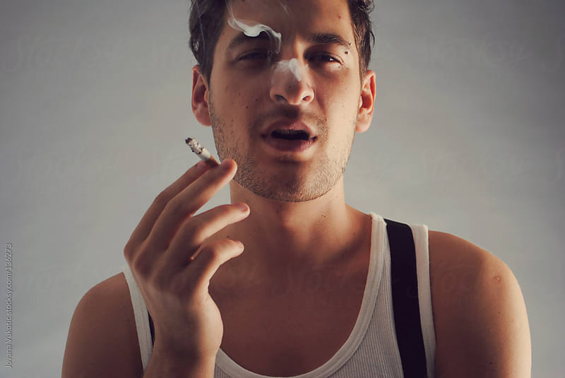 young man smoking by Jovana Vukotic for Stocksy United