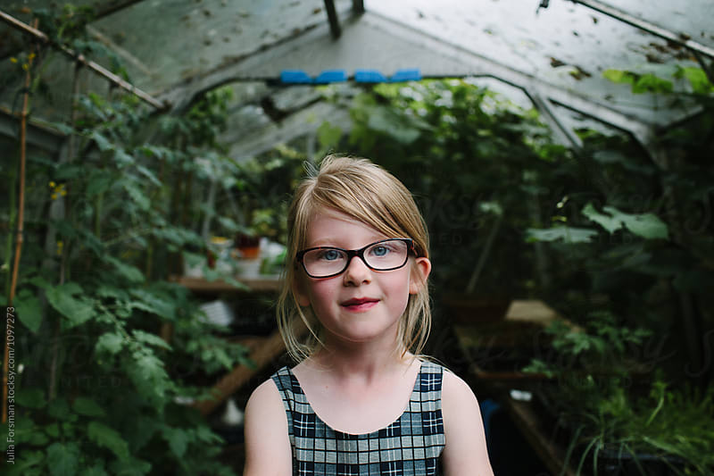 Portrait of young girl with long blonde hair and glasses standing in a greenhouse. by Julia Forsman for Stocksy United