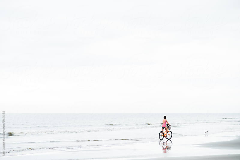 young girl riding her bike on the beach by Léa Jones for Stocksy United