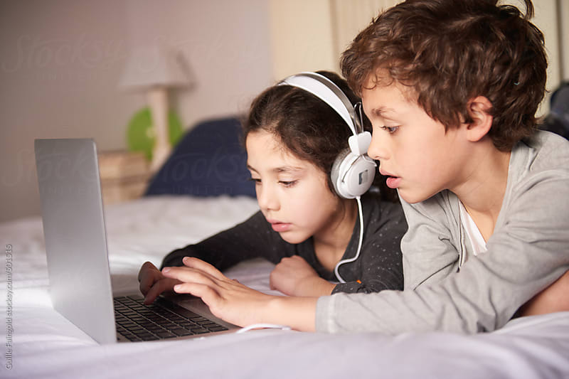 2 young brothers using the laptop and playing with their puppy by Guille Faingold for Stocksy United