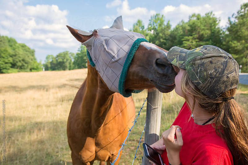 Country girl getting a kiss from a horse on the side of the road by Carolyn Lagattuta for Stocksy United