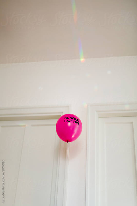 Fluo magenta balloon sayin Be wild. Have fun. flies inside bright room by Laura Stolfi for Stocksy United