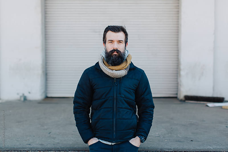 Portrait of a cool guy with a big beard standing by a warehouse by Jakob for Stocksy United