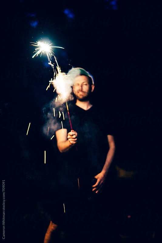Drunk guy acting silly with a sparkler and a beer by Cameron Whitman for Stocksy United