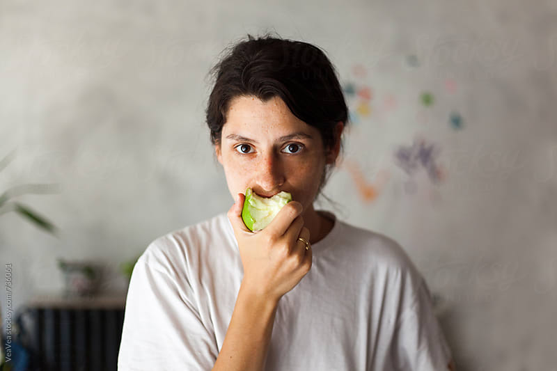 Young woman eating an apple by VeaVea for Stocksy United