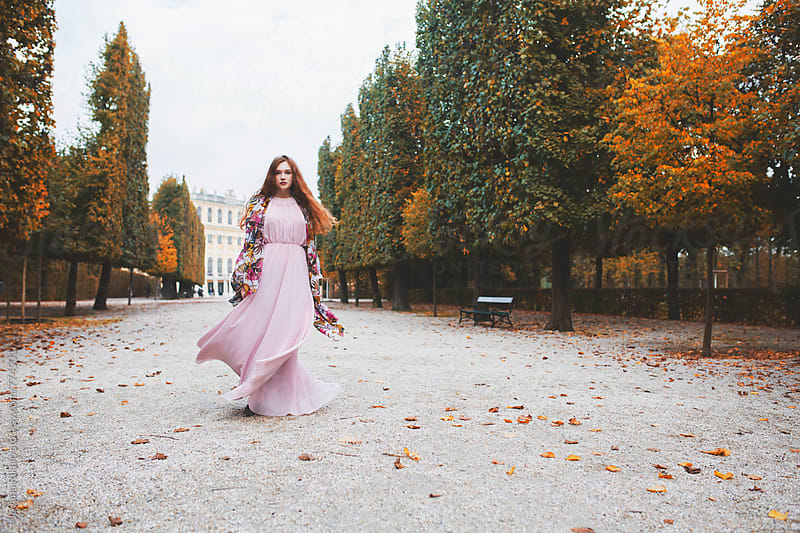 Young woman in a long pink dress; autumn season by Jovana Rikalo for Stocksy United