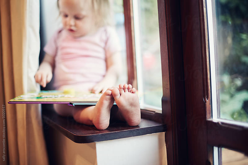 Child sat by the window reading by sally anscombe for Stocksy United