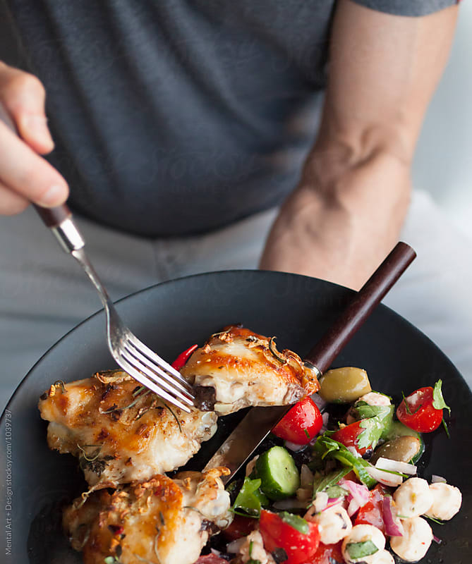 Lime and ginger roasted chicken thighs and tomato salad . by Mental Art + Design for Stocksy United