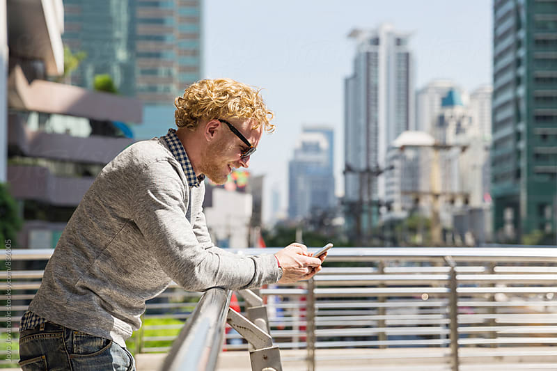Young handsome man checking his phone in the city by Jovo Jovanovic for Stocksy United