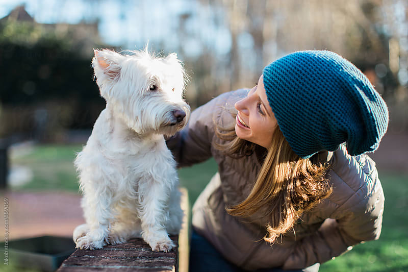 A beautiful woman talking a cute small white dog by Jakob for Stocksy United