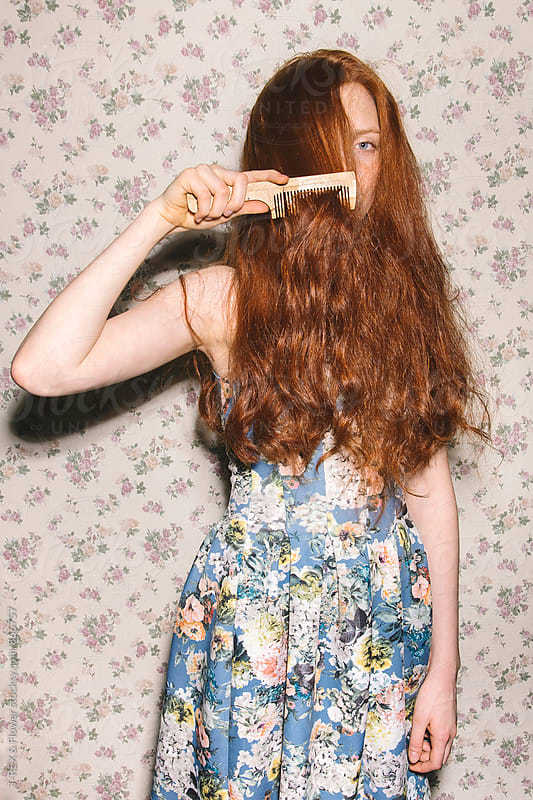 Young red-headed woman combing her hair by Danil Nevsky for Stocksy United