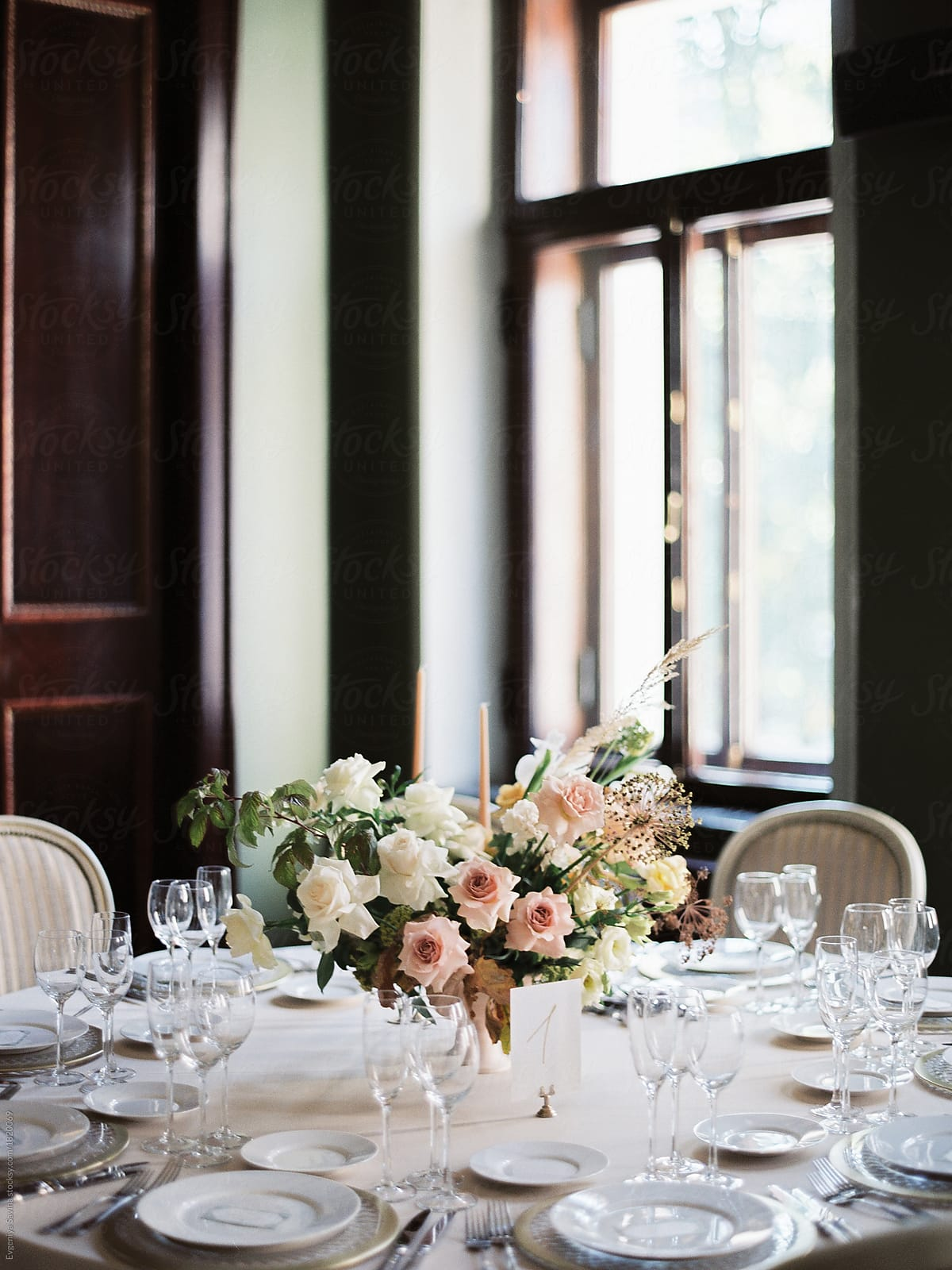 A beautiful wedding table setting with a floral composition with ...