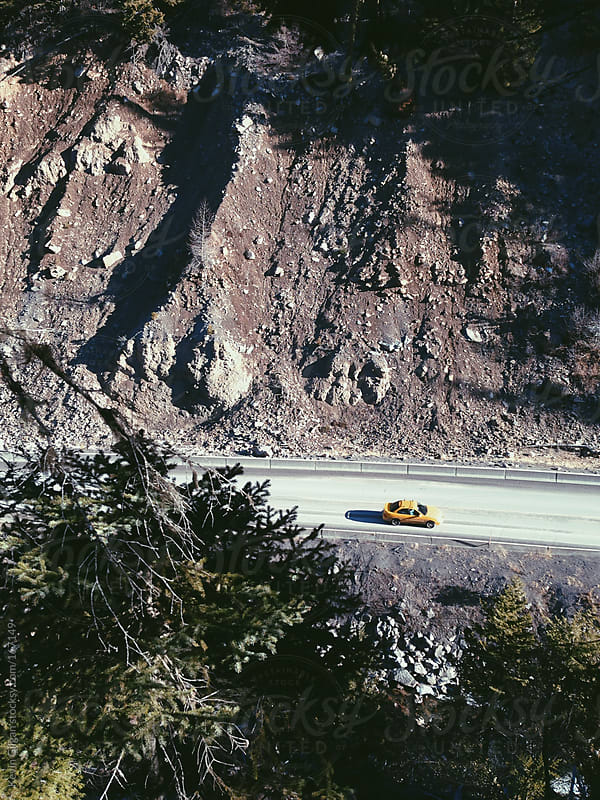 Yellow car drives through mountain pass by Kevin Gilgan for Stocksy United