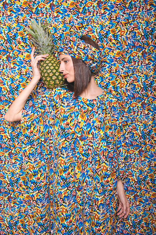Woman with pineapple against of patterned background by Danil Nevsky for Stocksy United